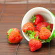 Stock Photo: Cup and strawberries on bamboo mat