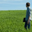 Stock Photo: Young mstanding with laptop in green field