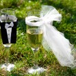 Two glasses of champagne in the clothes of bride and groom stand — Stock Photo