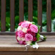 Beautiful bridal bouquet lying on the wooden benches — Stock Photo