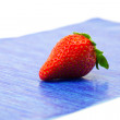 Strawberries lying on blue paper — Stok fotoğraf