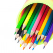 Colorful toy spring and colored pencils isolated on white - Stock Photo