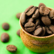 Small pot of coffee beans on green matter — Stock Photo #6058889