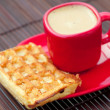 Waffles and cappuccino on a bamboo mat — Stock Photo