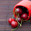 Cherry in the cup on a bamboo mat — Stock Photo