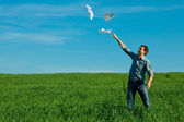 Young man throwing a paper in the green field — Stock Photo