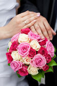 The hands of the bride and groom lying on the bridal bouquet — Stock Photo
