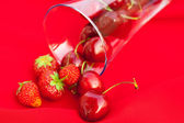 Glass of cherry and strawberry on a red background — Stock Photo
