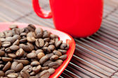 Cup and saucer and coffee beans on a bamboo mat — Stock Photo