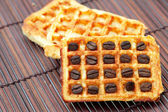 Waffles and coffee beans on a bamboo mat — Stock Photo