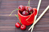 Cherry cup and chopsticks on bamboo mat — Stock Photo