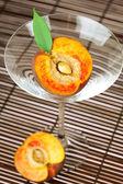 Broskev v martini sklenice na bambusové rohoži — Stock fotografie