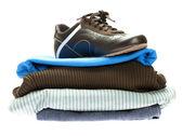Skor och ett berg av kläder isolerad på vit — Stockfoto