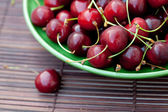 Plate of cherries on a bamboo mat — Stock Photo