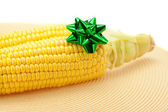 Corn lying on litter and gift bow isolated on white — Stock Photo