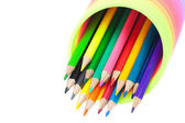 Colorful toy spring and colored pencils isolated on white — Stock Photo