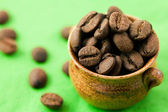Small pot of coffee beans on the green matter — Stock Photo