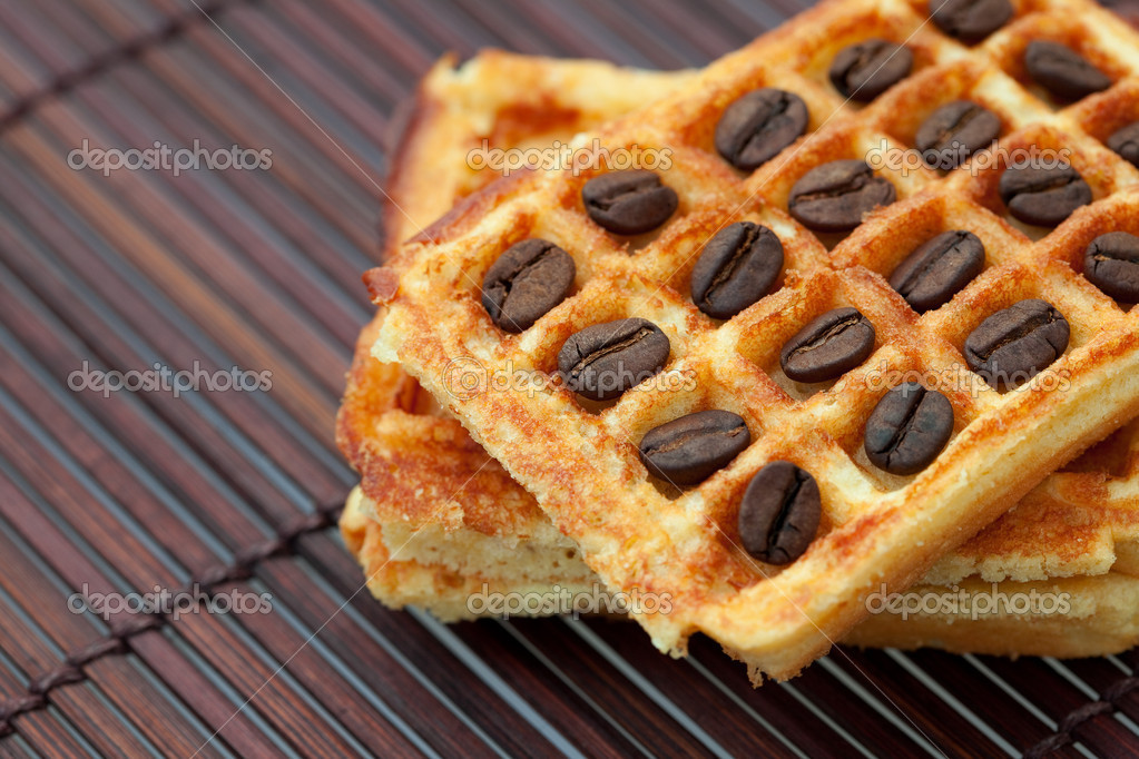 Coffee beans and waffles on a bamboo mat — Stock Photo #6059110