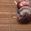 Plum on a bamboo mat — Stockfoto