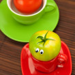 Tomato with eyes in the cup on a bamboo mat — Stock Photo