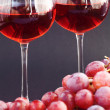 Stock Photo: Glass of wine and bunch of grapes on black background