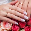 Stock Photo: Hands of the bride and groom with the rings lying on the bouquet