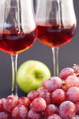 A glass of wine, apple and grape on a black background — Stock Photo