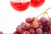Glass of wine and a bunch of grapes isolated on white — Stock Photo