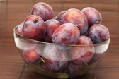 Plums in a glass bowl on a bamboo mat — Stock Photo
