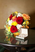 Bridal bouquet and a ring on the table — Stock Photo