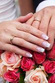 Manos de los novios con los anillos en el ramo — Foto de Stock