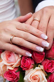 Ręce panny młodej i pana młodego z pierścieniami leżącego na bukiet — Zdjęcie stockowe