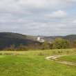 Field on the background of a medieval castle and the hills - Stockfoto