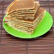 Stock Photo: Pancakes on plate on bamboo mat