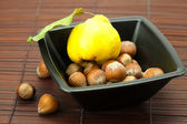 Hazelnuts in a bowl and quinces on a bamboo mat — Stock Photo