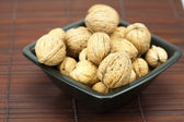 Walnuts in a bowl on a bamboo mat — Stock Photo