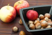Hazelnuts in a bowl and apples on a bamboo mat — Stock Photo