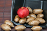 Pecans and apples in a bowl on a bamboo mat — Stock Photo