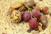 Nuts and grapes on a wicker mat — Stock Photo