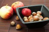 Hasselnötter i en skål och äpplen på en bambu matta — Stockfoto