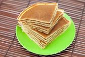Panqueques en un plato sobre una estera de bambú — Foto de Stock