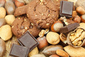 Oatmeal cookies, chocolate and nuts on a wicker mat — Stock Photo