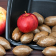 Stock Photo: Pecans and apples in bowl on bamboo mat
