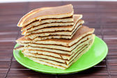 Pancakes on a plate on a bamboo mat — Stock Photo