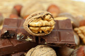 Bar of chocolate and nuts on a wicker mat — Stock Photo