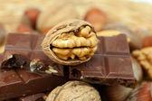 Barre de chocolat et les noix sur une natte en osier — Photo