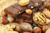 Bar of chocolate and nuts on a wicker mat — Stockfoto