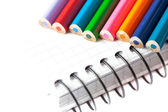 Colored pencils and a notebook isolated on white — Stock Photo