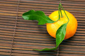 Mandarin with green leaves on a bamboo mat — Stock Photo