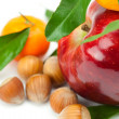Red apple, mandarin with green leaves and nuts isolated on whi — Stock Photo